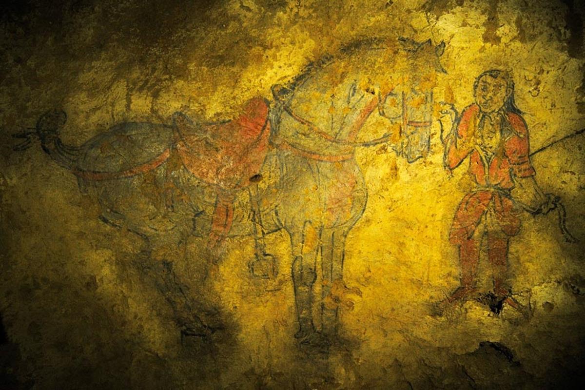 Koridorun 42 metrelik duvarındaki resimlerin arasında iki at ve süvarileri de bulunuyor. Atların biri kırmızı, diğeri gri-siyah. Koşumları da bütün detaylarıyla tasvir edilmiş. Atın kuyruğu bağlı, yelesi üç dişli olarak kesilmiş. Bu gelenek sadece Göktürklere ait. Bu tür at tasvirlerine bozkırdaki kaya resimleri ve kabartmalarda da rastlanıyor. Bunlar ölen kağanın atları; öbür dünyada da kullanması düşünceyle çizilmiş. Atların yanındaki adamların ise yüzleri ve elbiseleri farklı. O dönemdeki Göktürklerin giyiniş tarzı hakkında detaylı bilgi veriyor. Duvar resimlerinin hepsini Türk kökenli ressamlar çizmiş olmalı. Çünkü resimlerde başka bir kültüre ve geleneğe ait herhangi bir detay bulunmuyor. Eserler ayrıca Göktürklerde resim sanatının ne kadar gelişmiş olduğunu da gösteriyor.