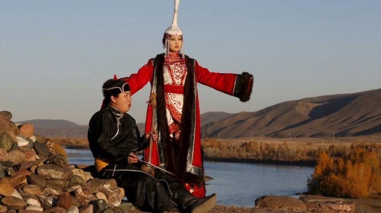 Boğazdan şarkı söyleme ustası ve ulusal kıyafetli kız Tuva Cumhuriyeti'ndeki Yenisey Irmağı'nın kıyısında.